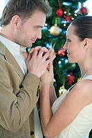 couple holding their hands next to christmas tree