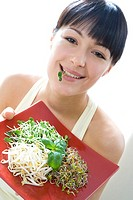 Toung woman with various sprouts on plate (thumbnail)