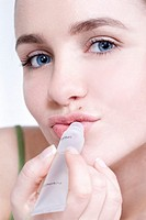 young woman applying lip balm