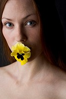 woman with yellow pansy in her mouth