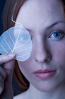 Woman covering eye with leaf (thumbnail)