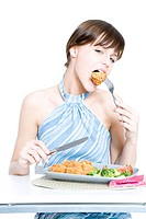 Young woman eating dinner (thumbnail)