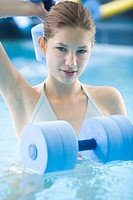 young woman doing exercise in swimming pool