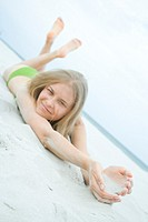 Smiling woman lying on beach (thumbnail)