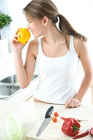 Woman in kitchen smelling ywllow pepper (thumbnail)