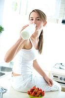 Woman drinking milk in kitchen (thumbnail)