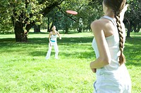 Young women playing frisbee