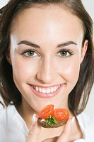 Young woman eating sandwich with cherry tomato