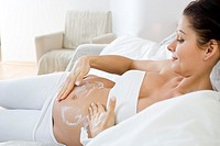 pregnant woman creaming her belly