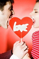 Couple eating heart shaped lollipop