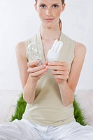Young woman holding two types of light bulbs (thumbnail)