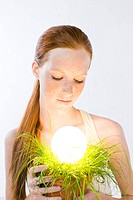 Woman with energy saving light bulb in plant (thumbnail)