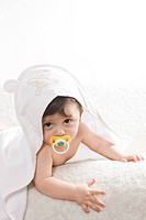 Baby in towel lying on sofa