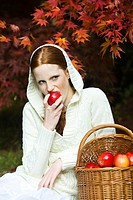 Young woman eating apple in park (thumbnail)