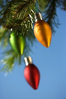 Red, green and orange ornaments hanging on Christmas tree branch against blue background (thumbnail)