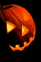 Carved Halloween pumpkin glowing in the dark (thumbnail)