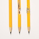 Whole pencil, broken pencil and stapled together pencil lined up against white background