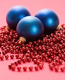 Still life of large blue Christmas ornaments and strings of red beads on red background