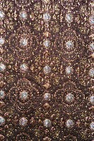 Close_up of textural vintage fabric with repetitive shapes and metalic thread stitching
