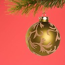 Still life of gold Christmas ornament hanging from pine branch