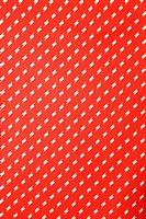 Close_up of vibrant red vintage fabric with repetitive white designs