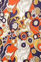 Close_up of vintage fabric with red blue and gold flowers and swirls printed on polyester