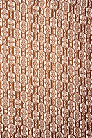 Close_up of woven vintage fabric with brown repetitive designs
