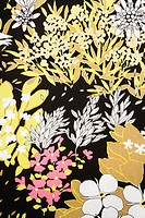 Close_up of vintage fabric with pattern of pink and golden flowers and leaves on polyester