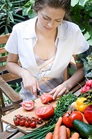 young woman cutting tomatoes