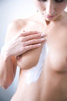 woman applying lotion on breast