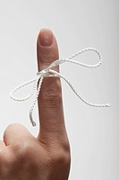 String tied on woman's index finger close_up