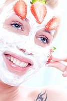 young woman with strawberry facial mask