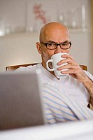 Mature man drinking a cup of coffee and looking at a laptop