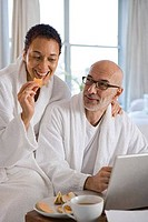 Mature woman having breakfast and sitting with a mature man working on a laptop