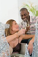 Close_up of a man and a woman toasting with champagne flutes