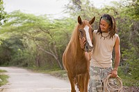 Hispanic man leading horse down dirt road