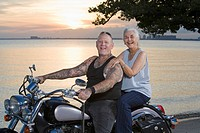 Mother and tattooed son riding motorcycle at the beach
