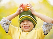Toothless Hispanic boy balancing apple on head