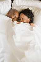 African couple in bed under blanket