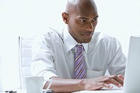 Mixed race businessman using laptop at desk