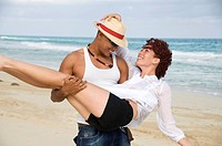 Man carrying young woman on beach, smiling, Havana, Cuba