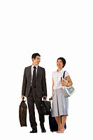 Businessman smiling at businesswoman with luggage, cut out (thumbnail)
