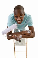 Young man holding paint roller, cut out (thumbnail)