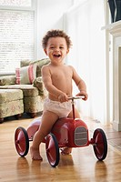 Mixed race boy riding on old-fashioned toy car (thumbnail)