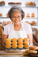 African woman holding muffins in bakery