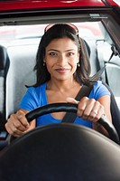 Smiling Indian woman driving car