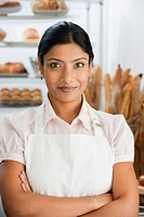 African woman with arms crossed in bakery