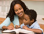 Mixed race mother helping son with homework