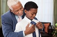 African man helping grandson tie necktie