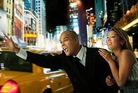 Couple in elegant clothing hailing taxi at night